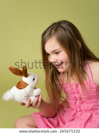 Happy smiling child, girl playing with Easter Bunny - stock photo