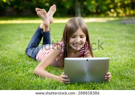 Happy smiling child lying on grass with digital tablet - stock photo