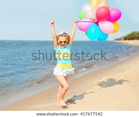 Happy smiling child on beach playing with colorful balloons near sea summer day - stock photo