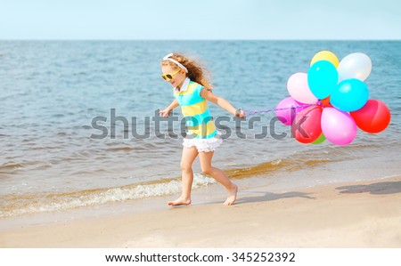 Happy smiling child on summer beach playing running with colorful balloons near sea - stock photo