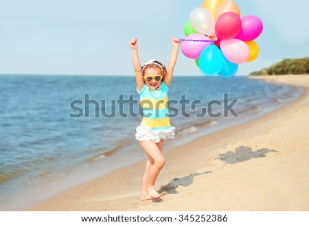 Happy smiling child on summer beach playing with colorful balloons near sea - stock photo