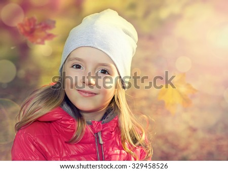 Happy smiling child outdoors on fall natural background. - stock photo