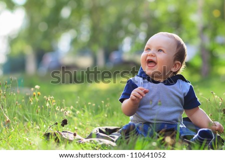 Happy smiling child sitting outdoors in summer park - stock photo