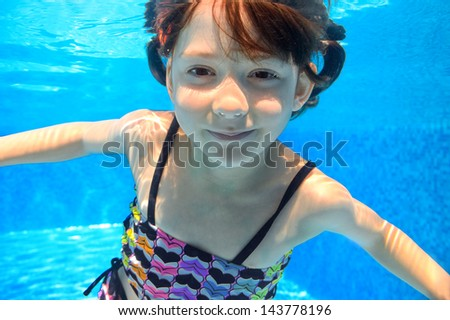 Happy smiling child swims underwater in pool, beautiful healthy girl swimming and having fun on family summer vacation, kids sport concept