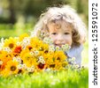 Happy smiling child with big bouquet of spring flowers lying on green grass - stock photo