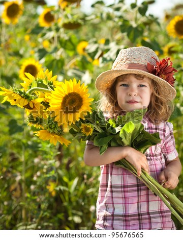 Happy smiling child with bunch of sunflowers in spring field - stock photo