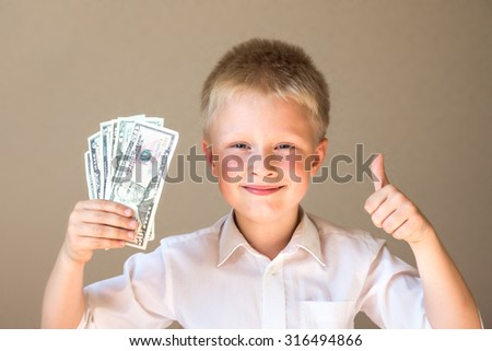 Happy smiling child with money (dollars) and thumb up on grey background - stock photo