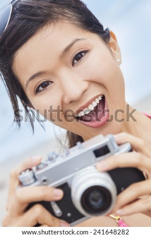 Happy smiling Chinese Asian young woman or girl in a bikini at the beach taking a photograph using a retro digital camera - stock photo