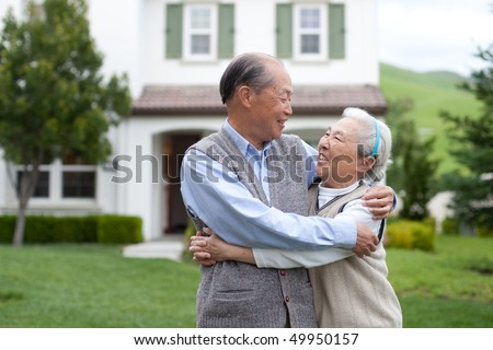 Happy Smiling Chinese Elderly Couple Standing in front of New House - stock photo