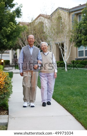 Happy Smiling Chinese Elderly Couple Walking in Residential Community - stock photo