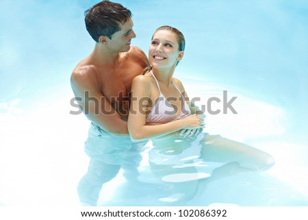 Happy smiling couple bathing together in swimming pool - stock photo