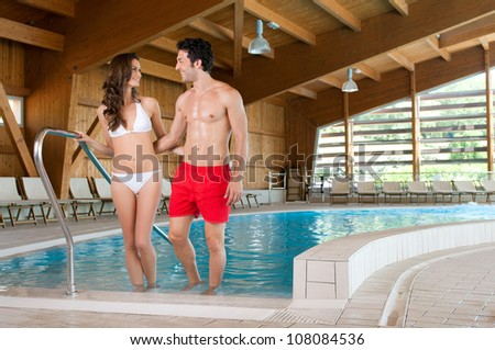 Happy smiling couple enjoy together a thermal pool in a spa centre - stock photo