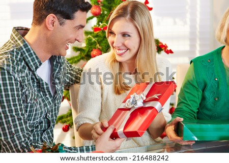 Happy smiling couple exchanging gifts at christmas eve - stock photo
