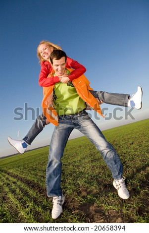 Happy smiling couple  jumping in sky above a green meadow - stock photo