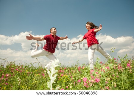 Happy smiling couple  jumping in sky above a green meadow