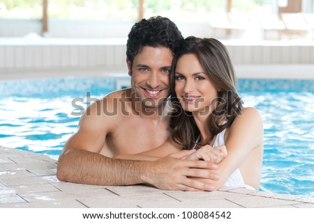 Happy smiling couple looking at camera while relaxing on the edge of a swimmingpool - stock photo