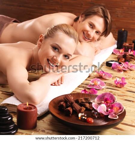 Happy smiling couple lying on the massage desks on the spa salon. Beauty treatment concept. - stock photo