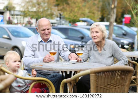 Happy smiling couple of seniors, a man and his wife, are enjoying glass of cold beer sitting with their granddaughter at the open air terrace of cozy cafe in the city center on a warm sunny day - stock photo