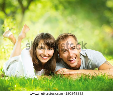 Happy Smiling Couple Outdoors. Relaxing on Green Grass. Park. Young Family Lying on Grass Outdoor. Nature - stock photo