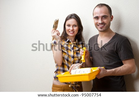 Happy smiling couple painting interior wall of home and having fun - stock photo