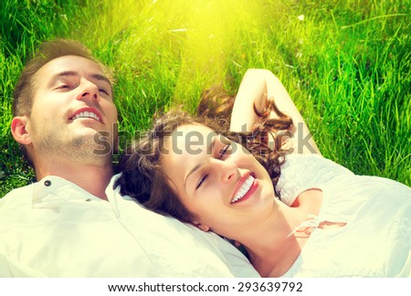 Happy Smiling Couple Relaxing on Green Grass. Park. Young Family Lying on Grass Outdoor. Happiness, relationships concept - stock photo