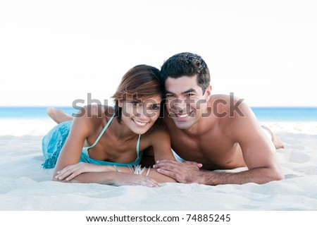 Happy smiling couple relaxing together and lying on sand at summer beach - stock photo