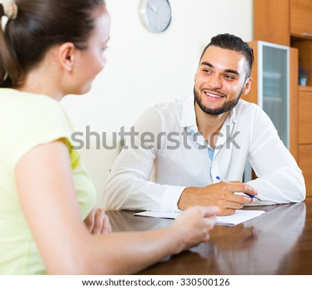 Happy smiling couple signing financial documents at the table at home
