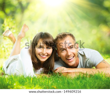 Happy Smiling Couple Together Relaxing on Green Grass. Park. Young Couple Lying on Grass Outdoor  - stock photo