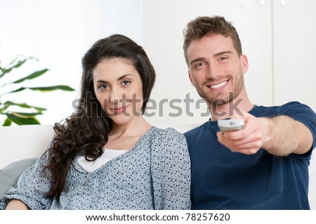 Happy smiling couple watching television at home - stock photo