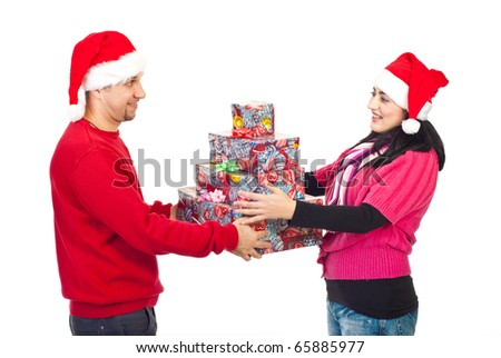 Happy smiling couple with Santa hats sharing Christmas gifts isolated on white background