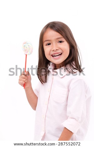 happy, smiling cute little girl eating marshmallow sweet candy - stock photo