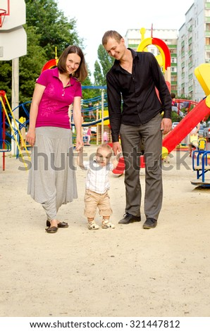 happy smiling daddy, mommy and little toddler son walking on playground outdoors - stock photo