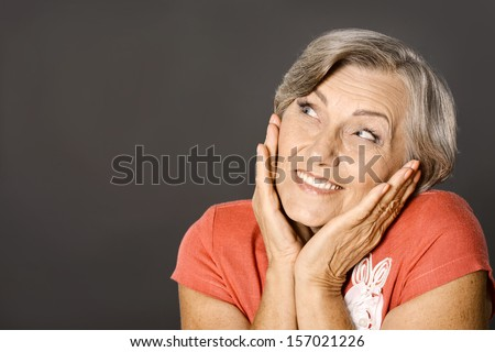 Happy smiling elderly woman portrait on grey background
