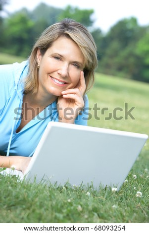 Happy smiling elderly woman working with laptop
