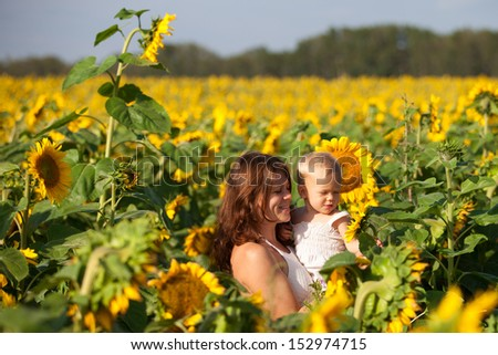 Happy smiling family having fun with sunflowers outdoors in summer on a sunny day.