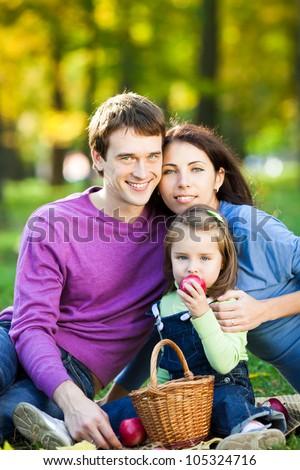 Happy smiling family having picnic in autumn park - stock photo