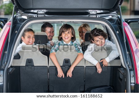 Happy smiling family in the car looking backwards through open trunk - stock photo