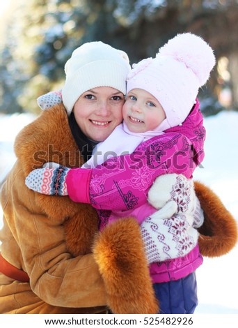 Happy smiling family mother and child daughter on a winter walk outdoors. Daughter and mother are happy together