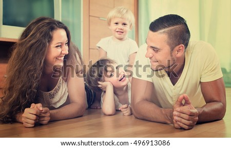 Happy smiling family of four enjoying time in living room at their home