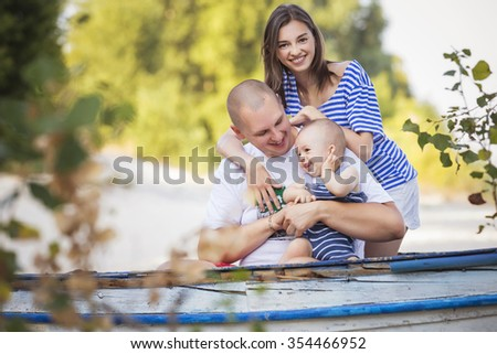 Happy smiling family of slim fit beautiful brunette mother, bold fat father and cute little infant baby on a seashore near nature in blue, white and red outfit: t-shirt and shorts. Summer. Copy space - stock photo