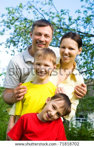 happy smiling family resting on the nature - stock photo