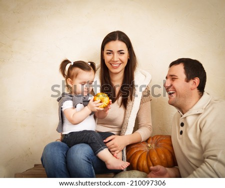 Happy smiling family with autumn pumpkin indoor - stock photo