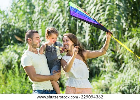Happy smiling family with child and toy kite at summer day  - stock photo