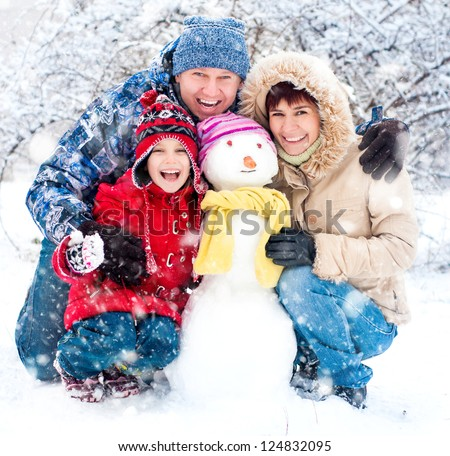 Happy smiling family with snowman winter portrait