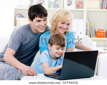Happy smiling family with son using laptop at home - indoors