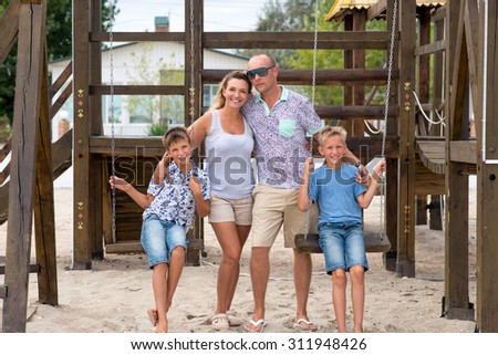 Happy smiling family with two children together at the playground. - stock photo