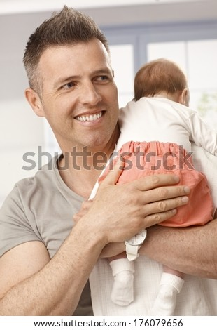 Happy smiling father holding newborn baby girl in arms, looking away.