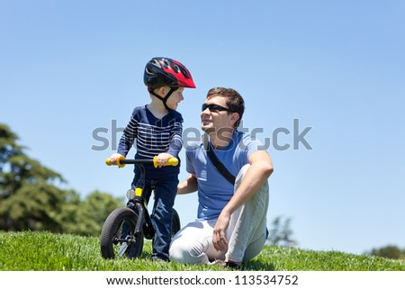 happy smiling father with his son on a balance bike - stock photo
