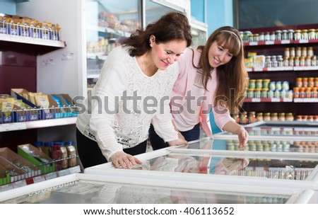 Happy smiling female buyers selecting frozen meat and vegetables at grocery 