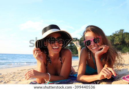Happy smiling female friends lying on tropical beach